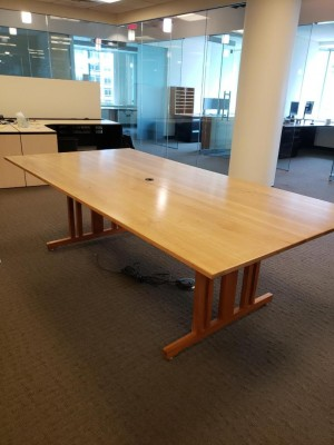 Light wood finish conference table with video electronics.